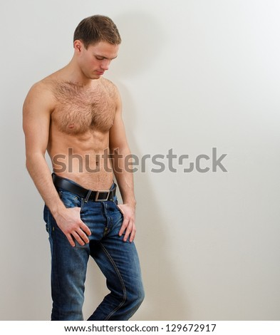 Young handsome guy in jeans with bare torso against the wall