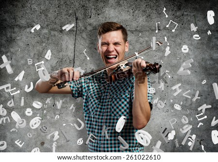 Young handsome guy on cement background with violin - stock photo