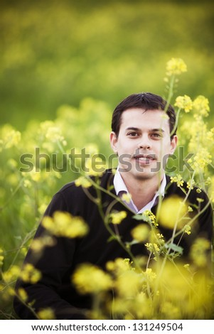 Young handsome guy on field staring at camera. - stock photo