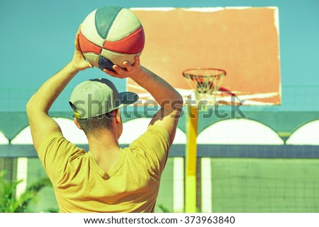 Young handsome guy playing basket on the beach -  Healthy lifestyle sport recreation concept - Vintage retro filter look  - stock photo
