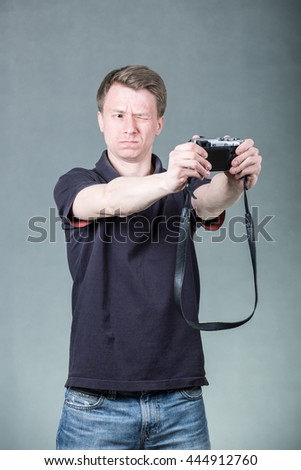 Young handsome guy taking selfie with retro style digital camera on grey background