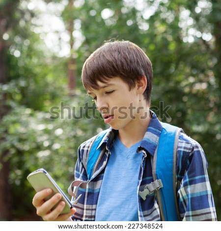 Young handsome happy modern teen talking on phone in summer park, outdoor, schoolboy - stock photo