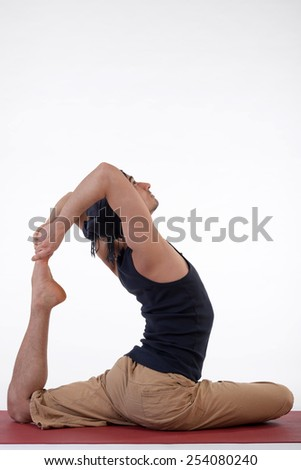 Young handsome healthy yoga man instructor doing yoga in photo studio on white isolated background. - stock photo