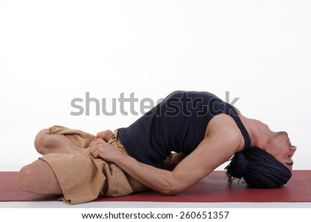 Young handsome healthy yoga man instructor doing yoga in photo studio on white isolated background.