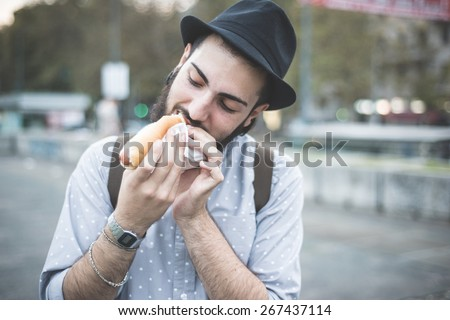 young handsome hipster gay modern man eating hot dog in town - stock photo