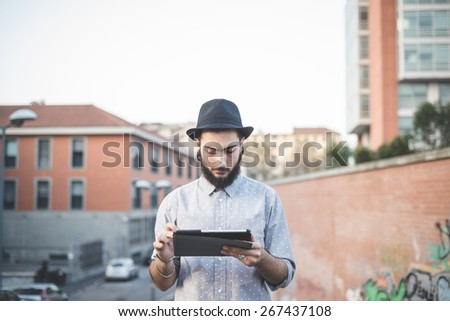 young handsome hipster gay modern man using tablet in town - stock photo