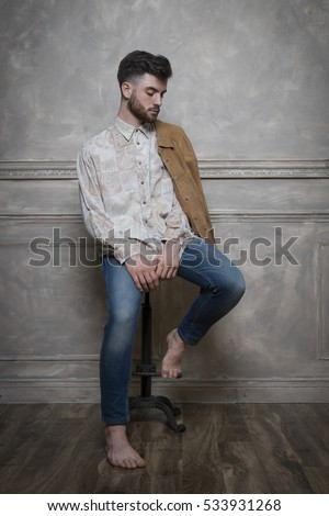 young handsome hipster man sitting on metal barstool in studio