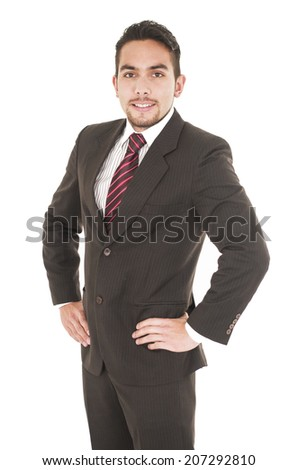 young handsome hispanic man in a suit with hands on the hip isolated on white