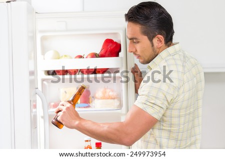 young handsome hispanic man looking for food in the fridge holding a bottle of beer - stock photo