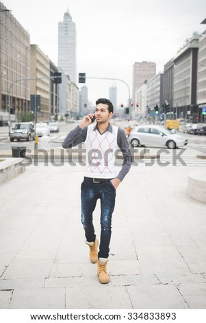 Young handsome indian contemporary business man walking through the city talking smartphone - technology, network, business, finance concepts