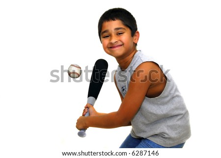 Young handsome indian kid having fun hitting ball - stock photo