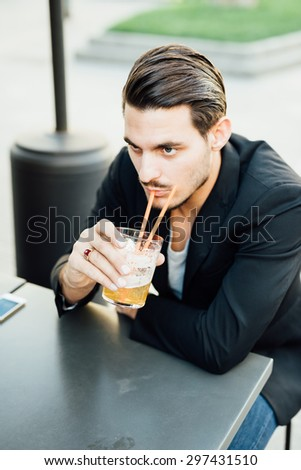 Young handsome italian boy having an happy hour seated on a bar in the city center