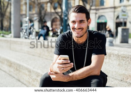 Young handsome italian boy seated on a sidewalk using a smart phone connected online - social network, technology concept - stock photo