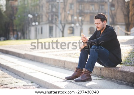 Young handsome italian boy seated on a sidewalk using a smartphone connected online - social network, technology concept - stock photo