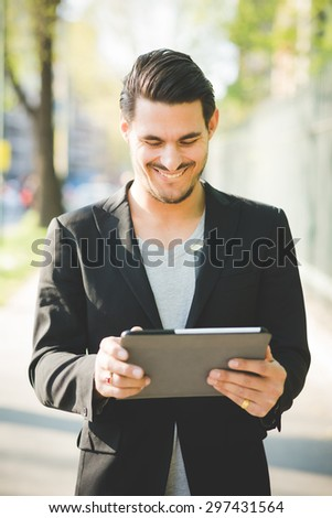 Young handsome italian boy walking through the city using a tablet connected online - technology, social network concept