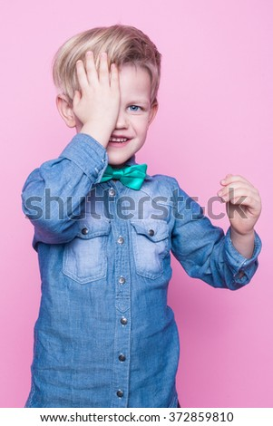 Young handsome kid smiling with blue shirt and butterfly tie. Studio portrait over pink background - stock photo