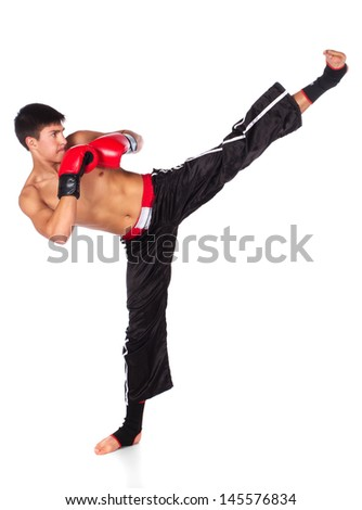 Young handsome male caucasian kickboxer wearing red boxing gloves and kickboxing gear isolated on a white background - stock photo