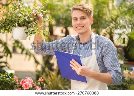 Young handsome male florist working in flowers shop.