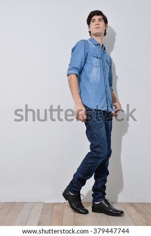 Young handsome male in jeans posing in full length over wooden background