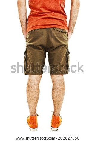 Young handsome male in shorts with hands in pockets from the back. Isolated on white background  - stock photo