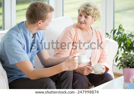 Young handsome male nurse and senior woman during tea time - stock photo