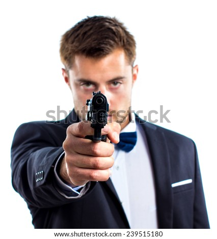 Young handsome man aiming at you with a gun - stock photo