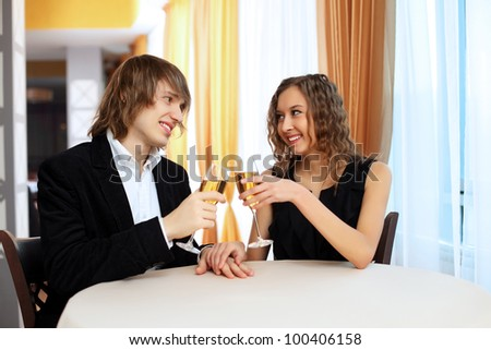 Young handsome man and pretty woman in a restaurant with shampagne