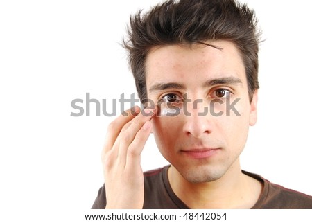 young handsome man applying eye cream (over white background)