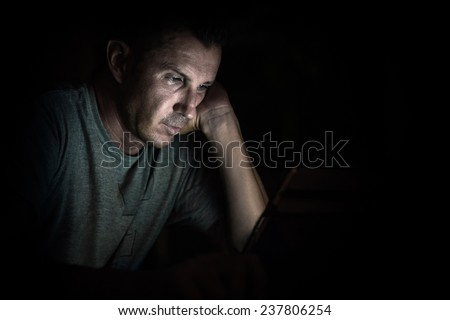 Young handsome man at laptop computer with light reflection from the screen to the face - Concept of alienation due to excess of working hours spent on a computer device and internet addiction - stock photo