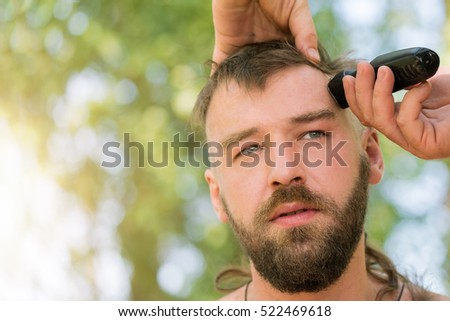 Young handsome man at the time of hair cutting with clipper