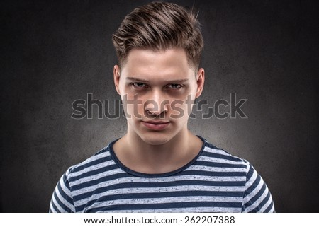 Young handsome man carefully looking straight ahead - stock photo
