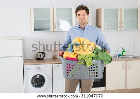 Young Handsome Man Carrying Basket With Heap Of Clothes In Kitchen - stock photo