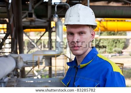 Young handsome man constructor in white hardhat and blue uniform. Close up portrait