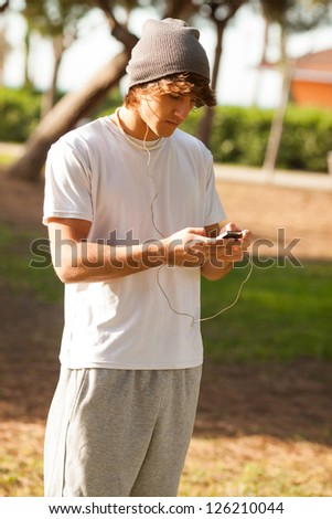 young handsome man consulting phone outdoors - stock photo