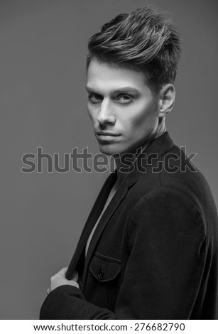 Young handsome man dressed casual posing in the studio. Black and white fashion portrait.