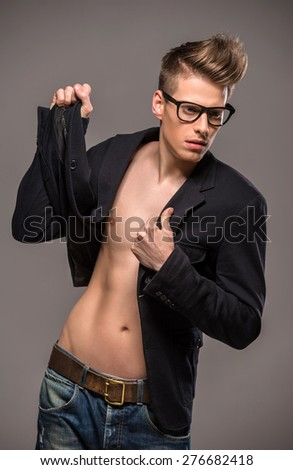 Young handsome man dressed casual posing in the studio on dark background. Fashion portrait.