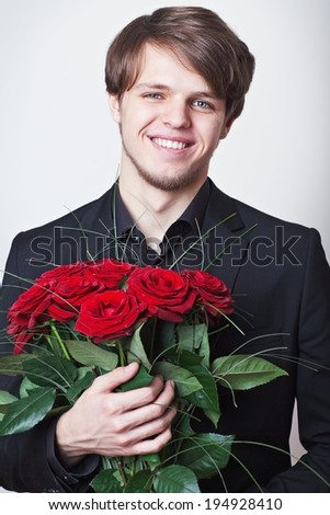Young handsome man dressed in a black suit with a bouquet of a red roses.  - stock photo