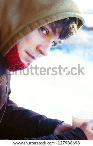 Young handsome man drinking hot drink in snowy winter morning outside - stock photo
