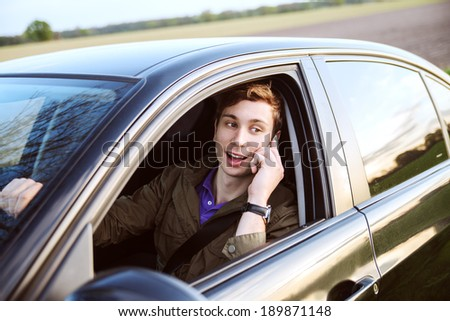 young handsome man driving car and speaking on mobile phone
