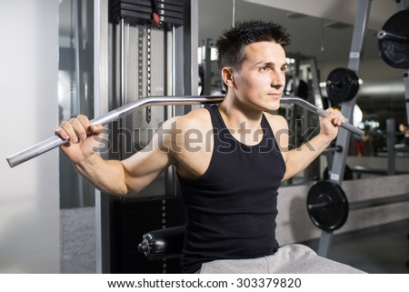 Young handsome man engaged in the gym - stock photo