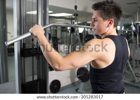 Young handsome man engaged in the gym