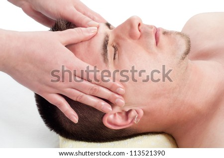 Young handsome man enjoying the facial massage on massage table. - stock photo