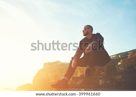 Young handsome man fashion model dressed in stylish clothes is enjoying warm day and leisure, while is sitting on stone rock against blue sky and sunshine with copy space background for your content - stock photo