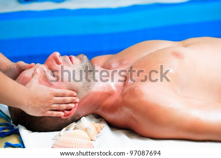 Young handsome man getting a massage. - stock photo