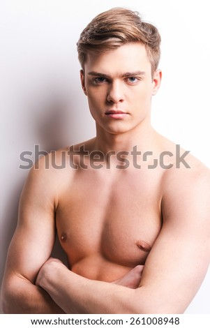 Young handsome man. Handsome young muscular man keeping arms crossed while standing against grey background - stock photo