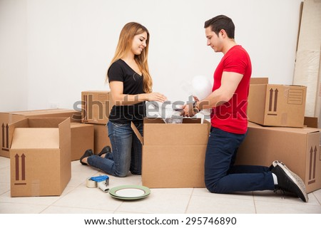 Young handsome man helping his girlfriend pack to move into his house