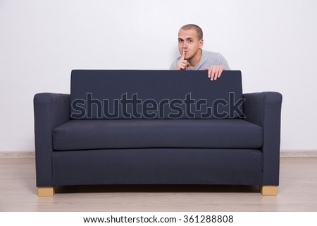 young handsome man hiding behind a sofa and showing shhh sign - stock photo