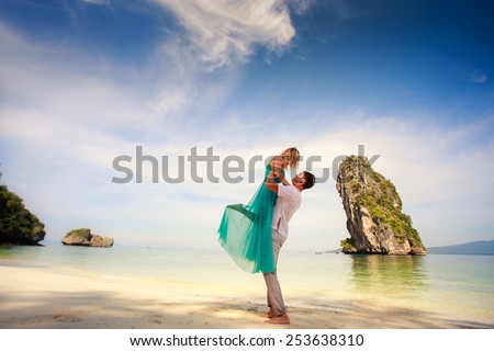 young handsome man hold up his beautiful blonde girlfriend in blue dress - stock photo