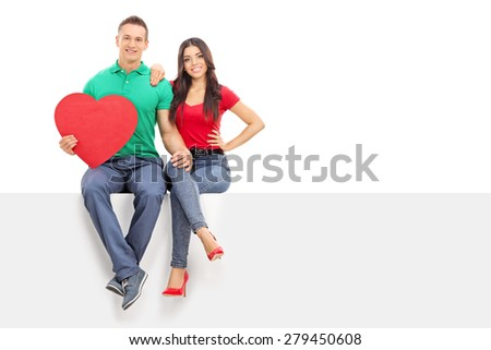 Young handsome man holding a big red heart seated on a blank billboard with his girlfriend isolated on white background - stock photo
