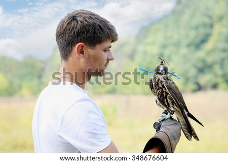 Young handsome man holding a falcon on his arm - stock photo